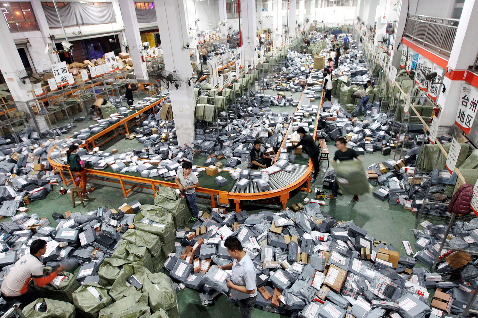 """Chinese workers sort parcels, most of which are from online shopping, at a distribution center of STO Express in Wenzhou city, east China's Zhejiang province, 12 November 2014. China's largest Internet retailer rang up more than $9 billion during the country's biggest online shopping holiday, smashing last year's figure to set a record for a single day of sales. Analysts said the """"Singles' Day"""" figures from e-commerce giant Alibaba show a continuing shift to online shopping over brick-and-mortar stores at a time of slowing economic growth in China. Singles' Day was invented by Chinese college students in the 1990s as an anti-Valentine's Day when people could buy something for themselves. It was set for November 11 because of the date's four """"ones"""". But Hangzhou-based Alibaba Group, which is known for its retail sites Taobao and Tmall.com, turned it into a day of online shopping for all with bargain deals. Other Chinese online retailers also have followed suit. In 2012, Alibaba posted sales totaling $3 billion on the Singles' Day, surpassing Cyber Monday in the United States. Last year's total was $5.71 billion. Alibaba Group announced this year's record sales of 57.1 billion yuan ($9.32 billion) for Tuesday shortly after midnight. During Singles' Day, a giant screen at the company's headquarters shows the sales figures updating in real time"""
